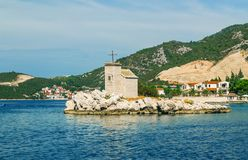 Small white church on the island in Klek, Adriatic sea and high mountains in the background Stock Photo