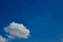 Small white cloud in blue sky. A single small white cloud in a blue sky Stock Images