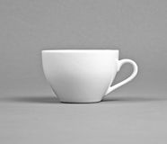 Small white coffee cup on a gray background. Stock Photo