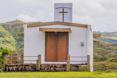 Small white country church in Guam. On a hillside with mountains and a cloudy sky in the background Stock Image