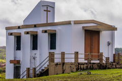Small white country church in Guam. Side view of a small white country church sitting on a hillside in Guam with cloudy sky in the background Stock Photos