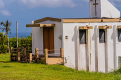 Small white country church in Guam. Side view of a small white country church sitting on a hillside in Guam with a view of the ocean under a cloudy sky in the Royalty Free Stock Image