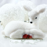 Small white deer and christmas decorations  background. Stock Photos