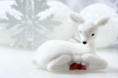 Small white deer and christmas decorations  background. Royalty Free Stock Photos