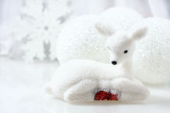 Small white deer and christmas decorations  background. Royalty Free Stock Images