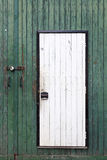 Small white door in large green barn door Stock Photography