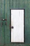 Small white door in large green barn door Stock Photography