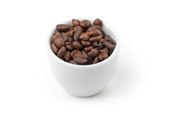Small white espresso cup full of fresh roasted coffee beans Stock Photography