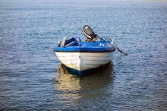 Small White Fibreglass Boat. Runabout, with outboard motor, moored in sea bay Royalty Free Stock Photos