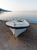 Small White Fishing Boat on Pebbly Beach, Greece. A small white traditionally designed fibreglass fishing boat on a pebbly Gulf of Corinth bay beach, in early Stock Images