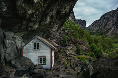 Small white, fishing house norway rock. Small white, fishing house norway mountains royalty free stock images