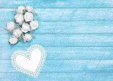 Small white flowers and paper heart with free space for text. Small white flowers with paper heart. Romantic wedding background, free space for text Royalty Free Stock Photography