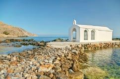 Small white Greek church on a tiny island in sea. Rocky path which leads to small Agios Nikolaos church in Georgioupolis on sunny summer morning, Chania, Crete Stock Photos