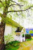 Small White House with Front Wood Porch. Beautiful scandinavian white small house with a nice front porch and a colorful garden, Norway Royalty Free Stock Photos