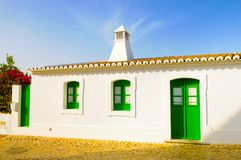 Small White House, Typical Portugal South Building, Travel Europe. A cute, small white house with closed green shutters windows on a whitewashed wall. Typical Stock Photos