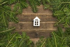 Small white house on wooden background. Frame of fir branches.  royalty free stock photo