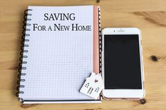 Saving for a New Home Concept with House ,Notebook and Phone Royalty Free Stock Image