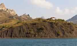 A small white hut on the high shore sea.Crimea Stock Images