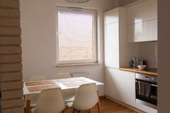 Small, white kitchen with table and new design chairs Stock Images