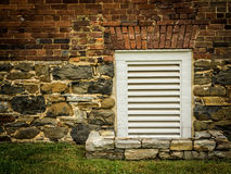 Small, White, Louvered Vent in Old Brick and Stone Wall Royalty Free Stock Photos