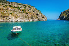 Small white motorboat anchored in sea bay. With clear azure water, Greece Royalty Free Stock Images