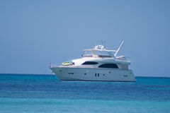 A small white motorboat. A motor-driven small kind of yacht, that is anchored in Front of the shore royalty free stock image