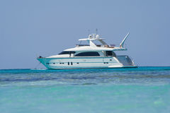 A small white motorboat. A motor-driven small kind of yacht, that is anchored in Front of the shore stock photography