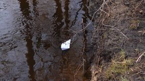 Small white paper boat floating on clear river in the autumn Park. Small white paper boat floating on clear river in autumn Park stock video footage