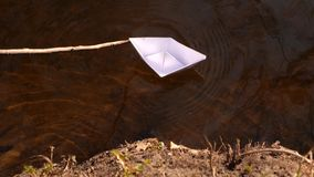Small white paper boat is flowing along the river. Small white paper boat is flowing along river stock footage
