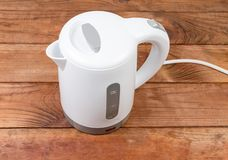 Small white plastic electric kettle on an old wooden table. Small white plastic electric kettle on an old rustic wooden table royalty free stock images