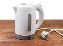 Small white plastic electric kettle on an old wooden table. Small white plastic electric kettle on an old rustic wooden table on a white background royalty free stock photo