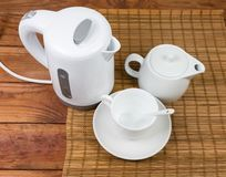 Plastic electric kettle, teapot and cup on old wooden table. Small white plastic electric kettle, white ceramic teapot and cup with saucer and spoon on the stock image