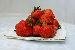 Small white plate, filled with succulent juicy fresh ripe red strawberries Royalty Free Stock Photo