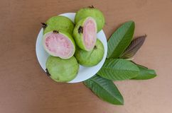 Top View Of Apple Guava Fruits And Leaves. Small white plate full of ripe guavas on a brown table top. Protruding from under the plate is a small stem of leaves vector illustration