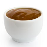 Small white pot of curry sauce dip, in perspective isolated on w Royalty Free Stock Photo