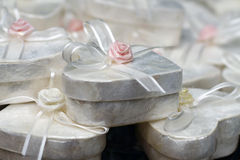 Small white present boxes. A close up a small white present boxes, in the shape of heart, with a rose on top Stock Images