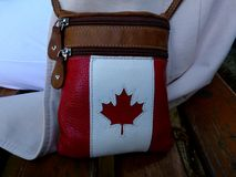 Red maple leaf symbol in white stitched leather woman`s purse royalty free stock photo