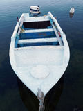 Small White Runabout Boat. A small white decked outboard motor runabout fishing boat, with motor and oars, and blue painted interior, moored in a small Greek Stock Image