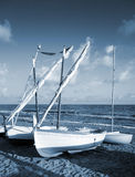 Small white sailing boats lay on the sandy beach Royalty Free Stock Image
