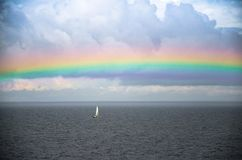 Small white sailing yacht and rainbow in Gulf of Finland, Baltic royalty free stock photo