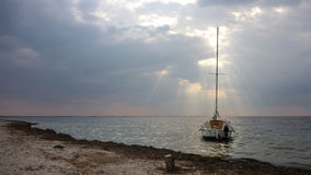 A small white sea yacht moored near the Black Sea shoreline Stock Image