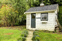 Small white shed with green door and window. Stock Images