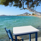 Small white table and chair overlooking the blue Aegean Sea Royalty Free Stock Photography