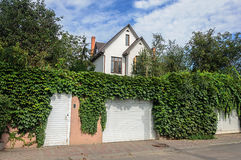 Small white two-storied residential house, fence with hops Stock Photos