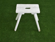 Small white wooden chair standing on green background Stock Photo
