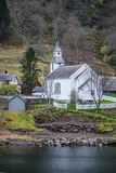 Small white wooden church on a fjord shore. Traditional small white wooden church on a shorephotographed from a Fjords sightseeing cruise boat leaving Flam in Stock Image