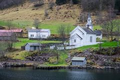 Small white wooden church on a fjord shore. Traditional small white wooden church on a shorephotographed from a Fjords sightseeing cruise boat leaving Flam in Stock Photos