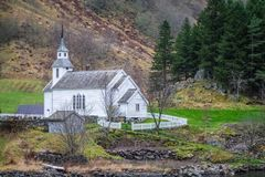 Small white wooden church on a fjord shore. Traditional small white wooden church on a shorephotographed from a Fjords sightseeing cruise boat leaving Flam in Stock Photo