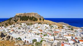 Small whitewashed village of Lindos with Acropolis at foot of mountain. Scenery of Rhodes island at Aegean sea. Dodecanese, Greece royalty free stock images