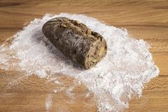 Small whole grain bread stick with freshly made walnuts. Small bar of wholemeal bread with freshly made walnuts next to some ingredients on a wooden table Stock Image